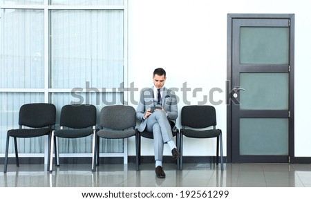 Ready for interview. Thoughtful  man in formalwear holding paper while sitting at the chair in waiting room  - stock photo