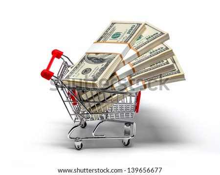 Ready for shopping - shopping cart full of stacks of dollar bills isolated on white