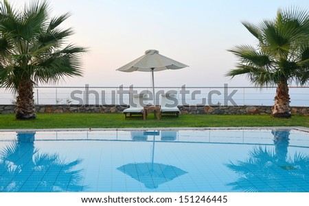 Ready for summer: sunbeds by the pool - Sunbeds, umbrella, and palm trees by the pool - stock photo