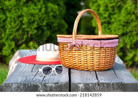 Ready for summer weekend. White sunglasses summer hat and wicker basket on wooden table. Summer park outdoors. - stock photo