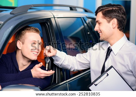 Ready for test drive. Handsome young car salesman giving key to smiling client to test a new luxury SUV while standing in automobile dealership - stock photo