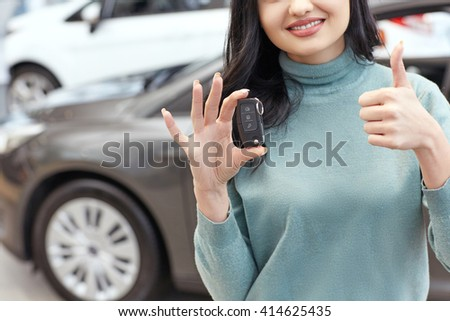 Ready for the road. Cropped closeup of a woman smiling cheerfully holding car keys showing thumbs up posing at the car salon - stock photo