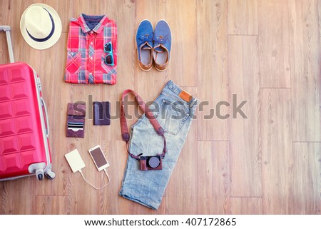 Ready for travel. Essentials for tourist. Different male clothes, accessories and gadgets on wooden floor. Valise, wallet, passport, smartphone and powerbank, shoes, camera, hat. - stock photo