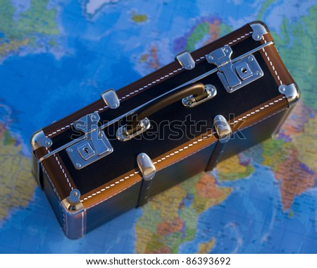 Ready for travel - old suitcase on blurred world map in background - stock photo
