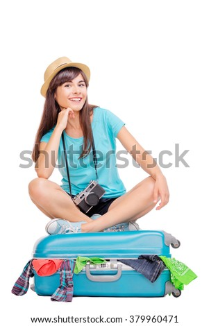 Ready for vacation. Traveling concept. Young happy woman sitting on the luggage valise. Isolated on white.