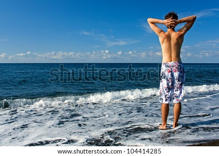 Ready for vocation. Young and healthy man wearing swimming trunks standing on the beach and looking at the sea. - stock photo