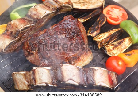 ready grilled beef meat fillet and asado ribs on bbq with garnish of tomatoes sweet bell pepper and eggplants - stock photo