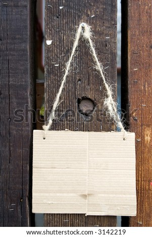 Ready made cardboard sign hanging against a wooden fence.