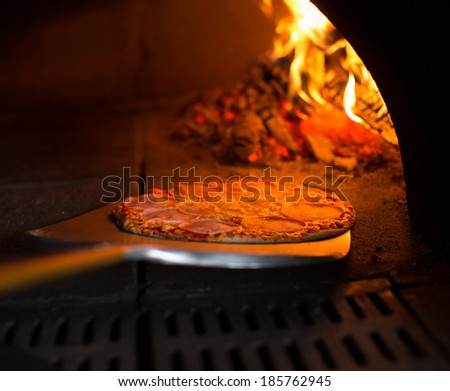Ready pizza getting from oven - stock photo