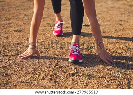 Ready steady girl. Young woman athlete in steady position on a dirt preparing to run outdoors on a sunset. Competition and sport lifestyle concept. Unrecognizable - stock photo