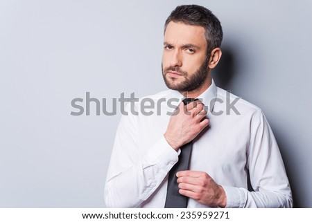 Ready to business meeting. Confident mature man adjusting his necktie and looking at camera while standing against grey background - stock photo
