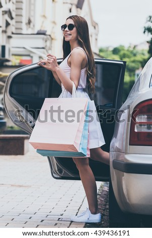 Ready to buy more. Beautiful young woman carrying shopping bags and smiling while standing near the car on the street - stock photo