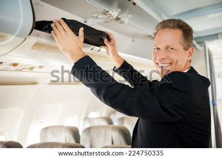 Ready to flight. Confident mature businessman preparing to flight while standing inside of airplane - stock photo