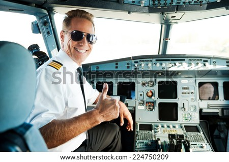 Ready to flight. Rear view of confident male pilot showing his thumb up and smiling while sitting in cockpit  - stock photo