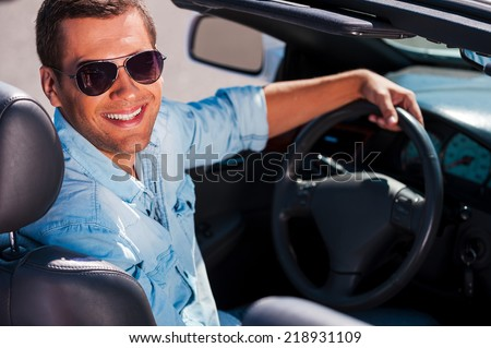 Ready to go. Handsome young man in sunglasses sitting on front seat of his convertible and smiling  - stock photo