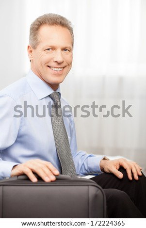 Ready to go. Smiling grey hair man in shirt and tie holding hand on suitcase while sitting on bed   - stock photo