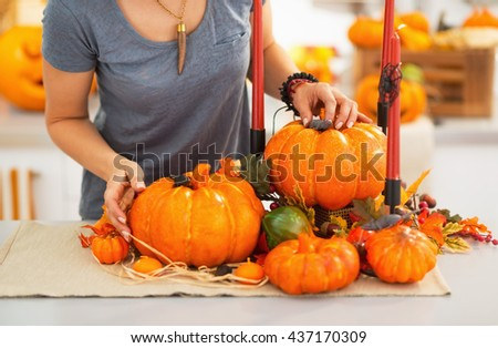Ready to halloween invasion. Closeup on young woman decorating kitchen for halloween.