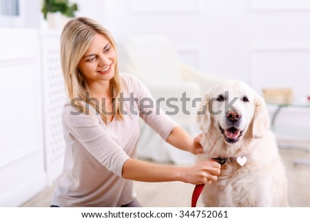 Ready to have a walk. Pleasant charming vivacious woman smiling and wearing the collar on the dog while feeling content