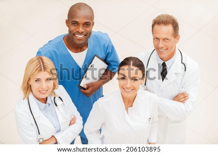 Ready to help you anytime. Top view of four confident doctors standing close to each other and smiling - stock photo