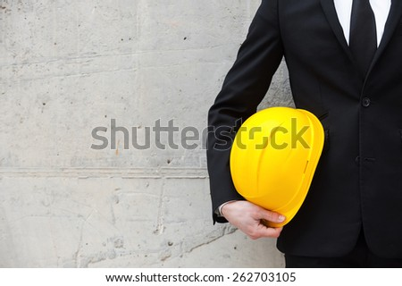 Ready to new project. Cropped image of man in formalwear holding hardhat while standing against the concrete wall - stock photo