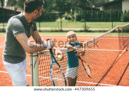 Ready to play? Cheerful father and daughter leaning at the tennis net and looking at each other with smiles  - stock photo