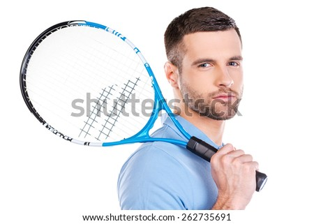 Ready to play. Confident young man holding tennis racket and looking at camera while standing against white background  - stock photo