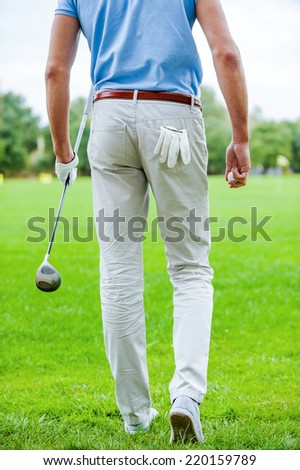 Ready to play golf. Rear view of male golfer walking away while holding golf ball and driver