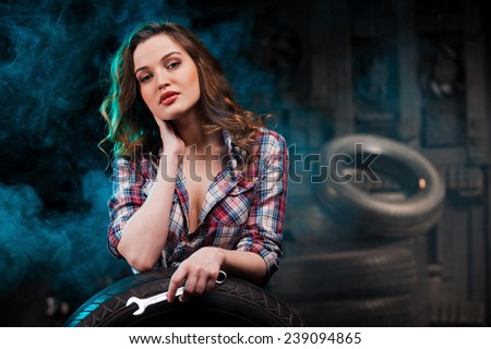 Ready to repair your car. Beautiful young woman holding work tool and looking at camera while leaning at the car tire in auto repair shop - stock photo
