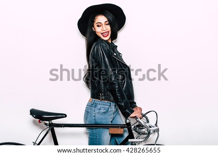 Ready to ride. Beautiful young mixed race woman in leather jacket and hat standing near black bicycle and looking away with smile - stock photo