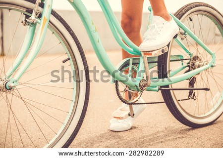 Ready to ride. Close-up of young woman holding her foot on bicycle pedal - stock photo