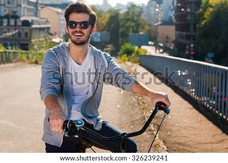 Ready to ride. Handsome young man on bicycle looking at camera and smiling while standing outdoors - stock photo