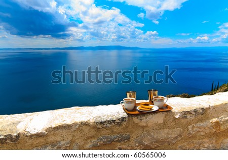Ready to serve cups of coffee and biscuits against a cloudy sky - stock photo