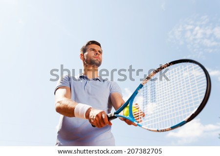 Ready to serve. Low angle view of handsome young man in polo shirt holding tennis racket and ball while standing against blue sky