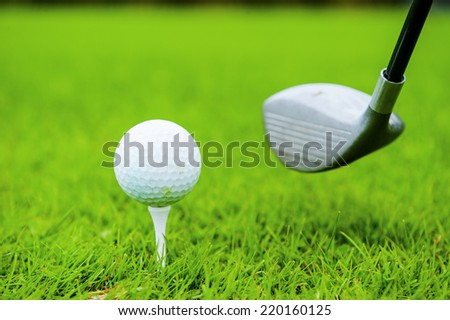 Ready to strike. Close-up of driver swinging near the golf ball