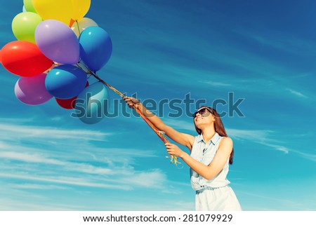 Ready to take off. Low angle view of cheerful young woman holding colorful balloons and smiling while standing against the blue sky - stock photo