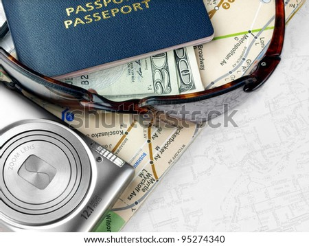 Ready to travel.  Travel necessities: sunglasses, passports camera, dollars on the map - stock photo