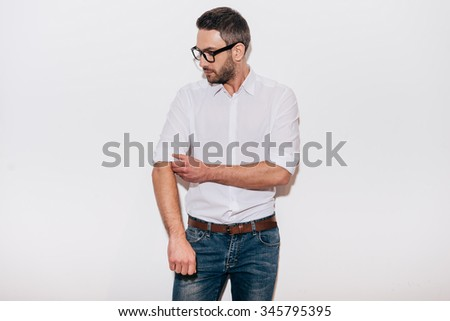 Ready to work. Confident mature man in white shirt adjusting his sleeve while standing against white background - stock photo