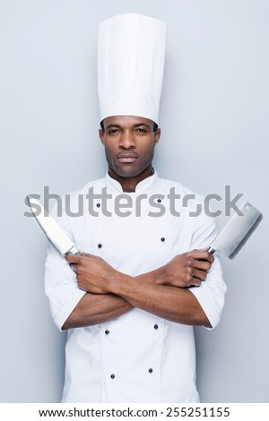 Ready to work. Confident young African chef in white uniform holding knifes in his hands and looking at camera while standing against grey background - stock photo