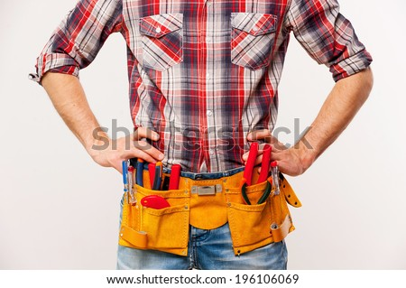 Ready to work. Handsome young handyman with tool belt holding hands on hip while standing against grey background