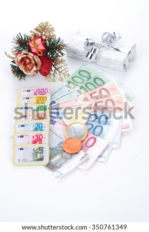 Real and fake money with Christmas gifts and chocolate - stock photo