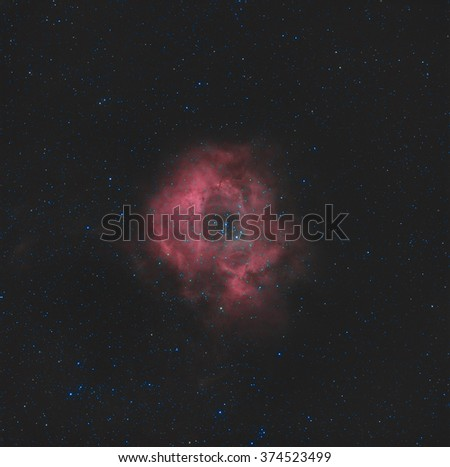 Real astronomic picture taken using telescope of the rosette nebula, a circular hydrogen cloud in the monoceros region of the milky way galaxy. The open cluster ngc 2244 is contained by the nebulosity - stock photo