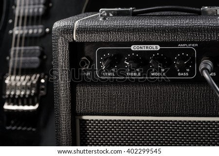 Real atmosphere of a concert because of cool black electric guitar and the black amp near it. Shot with a focus, the background is blurred. - stock photo