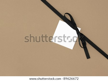 Real Brown Ribbon Bow with Blank Note card Tag on Plain Brown Background