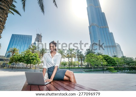 Real business in Dubai. Smiling African businesswoman businessman sitting in the street and working at a laptop in Dubai downtown among the skyscrapers - stock photo