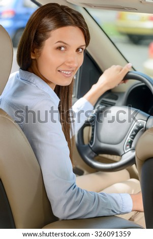 Real businesswoman. Nice appealing young woman holding a wheel and sitting in the car while expressing positivity