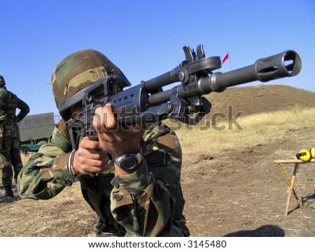 Real camouflaged soldier aiming. - stock photo