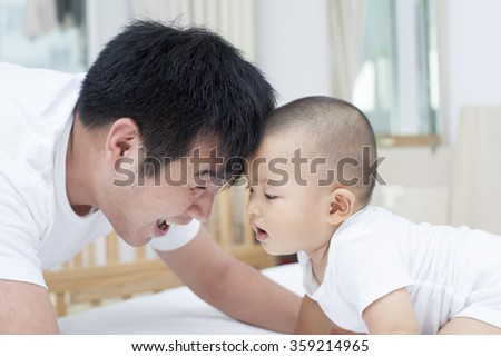 Real Chinese father and son playing in bed