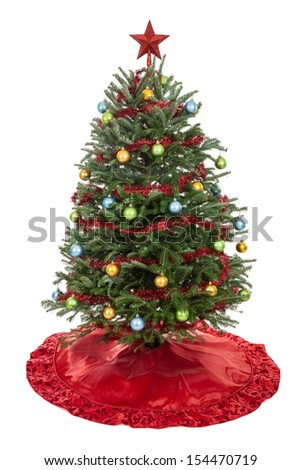Real decorated Christmas tree with skirt, garland, ornaments and star isolated on white - stock photo