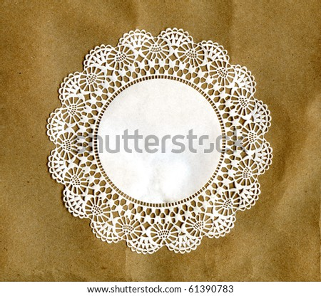 Real Doily Coaster On Brown Paper - stock photo