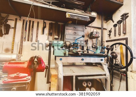 real domestic DIY home workshop full of tools, untidy, ready for work, detail of homemade lathe, retro vintage color tone - stock photo
